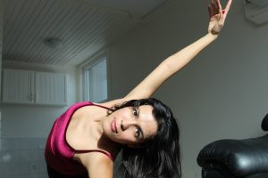 woman bending gracefully to the right, her arms outstretched and eyes staring into the camera.