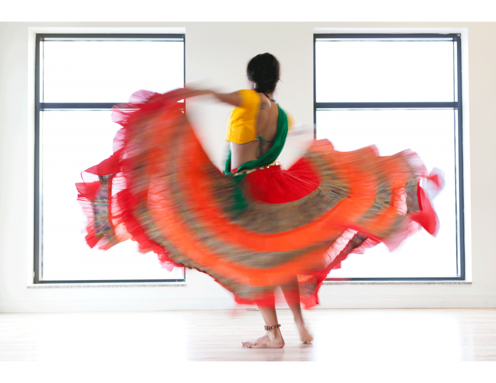 A photo of Shrina wearing a large, colourful circle skirt that is captured in motion. Her back is away from the camera as she twirls.